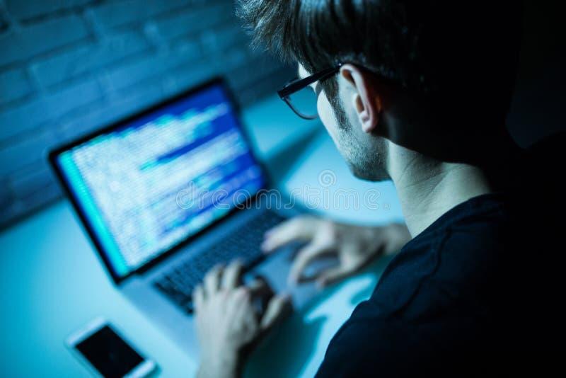 使用在膝上型计算机的人膝上型计算机文字编程的代码 年轻hacke 库存图片