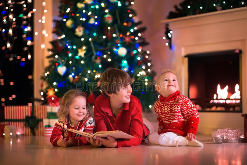 使用在自圣诞前夕的壁炉的孩子 免版税库存图片