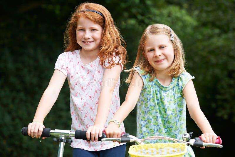 使用在自行车和滑行车的两个女孩户外 免版税库存图片