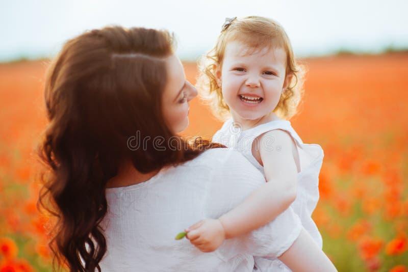 使用在花田的母亲和女儿 免版税库存照片