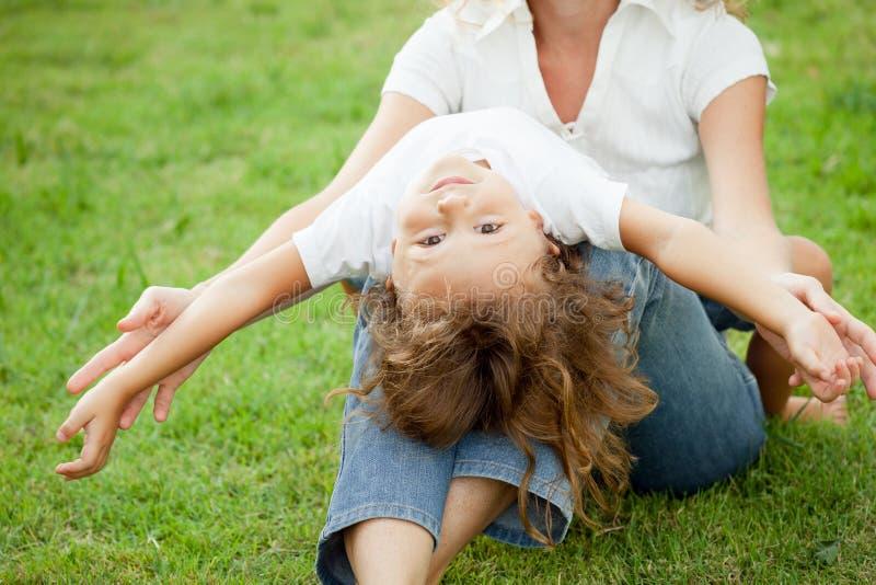 使用在草的母亲和儿子在天时间 免版税库存照片