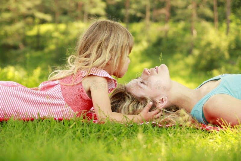 年轻使用在草的母亲和她的小女儿 图库摄影