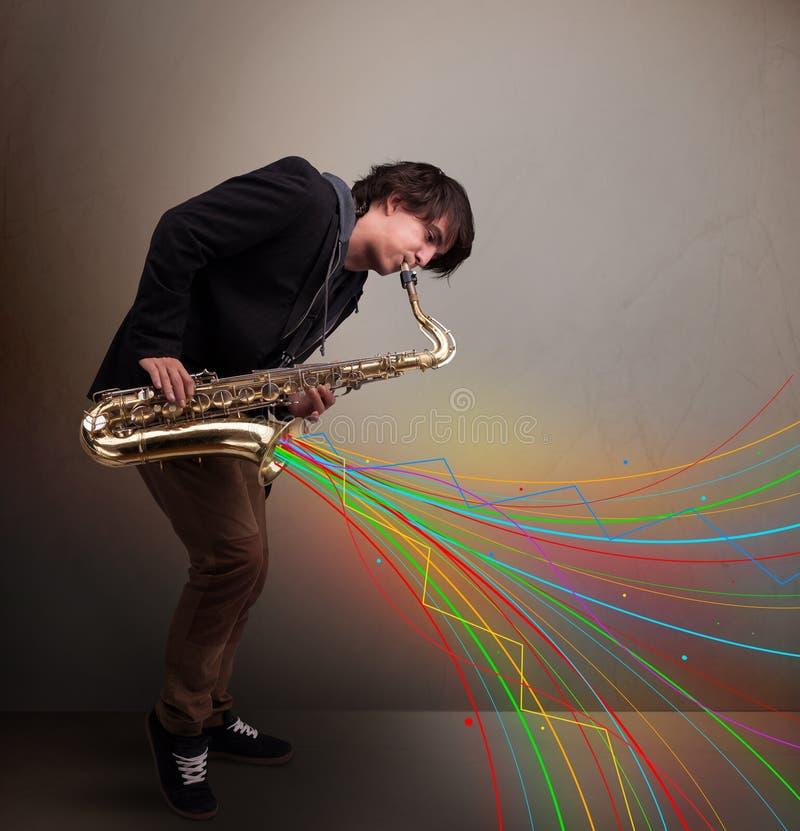 使用在萨克斯管的可爱的音乐家,当五颜六色的摘要时 免版税库存图片