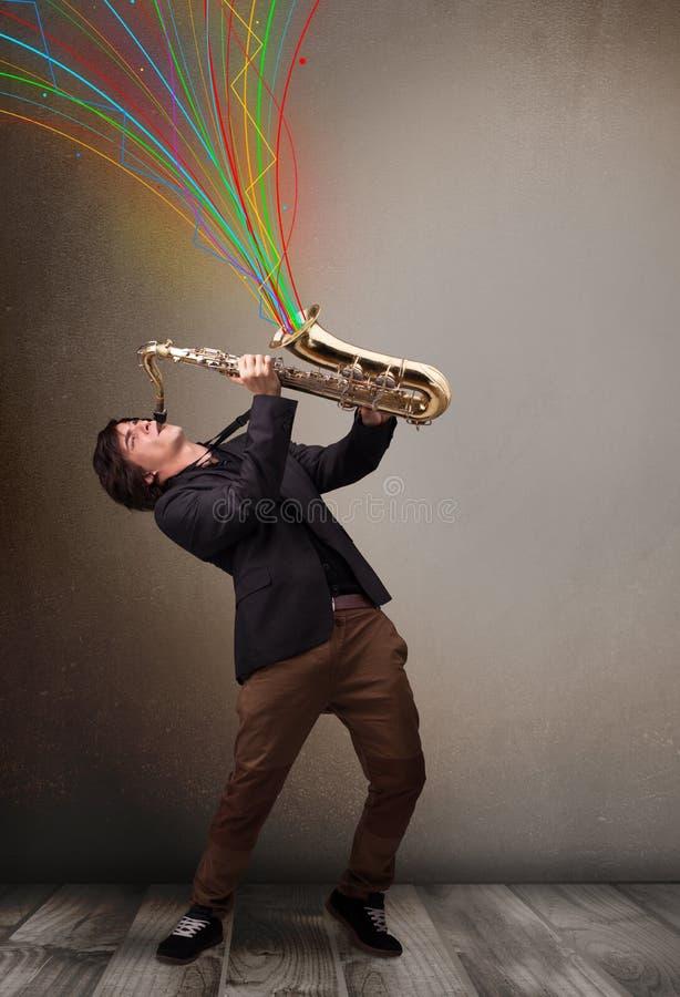 使用在萨克斯管的可爱的音乐家,当五颜六色的摘要时 库存照片