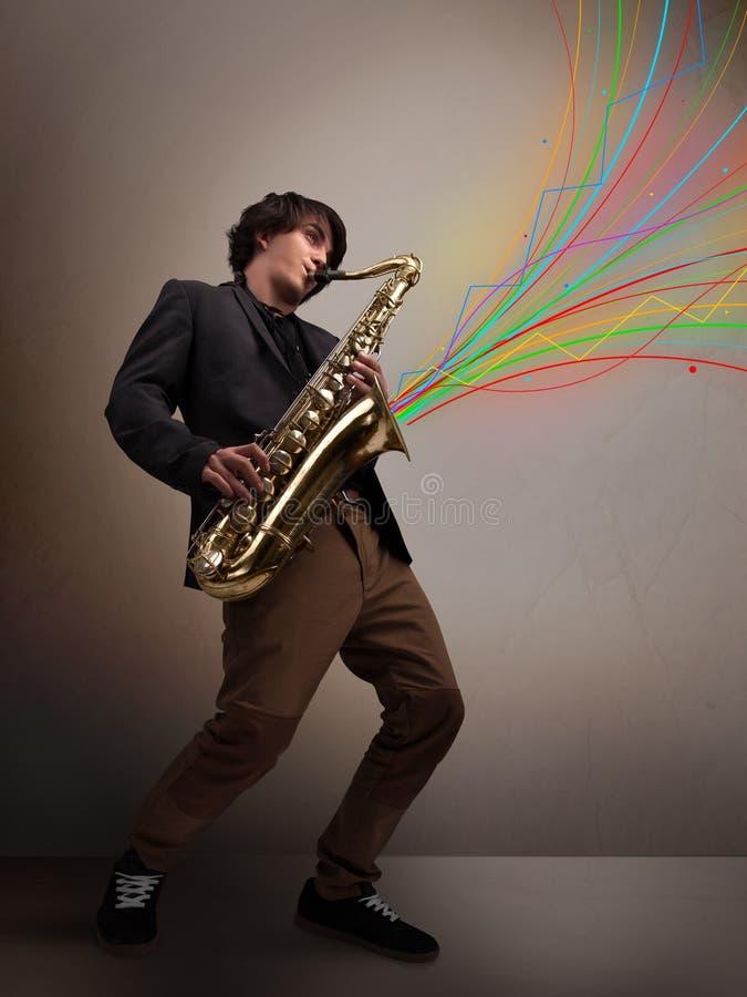 使用在萨克斯管的可爱的音乐家,当五颜六色的摘要时 图库摄影