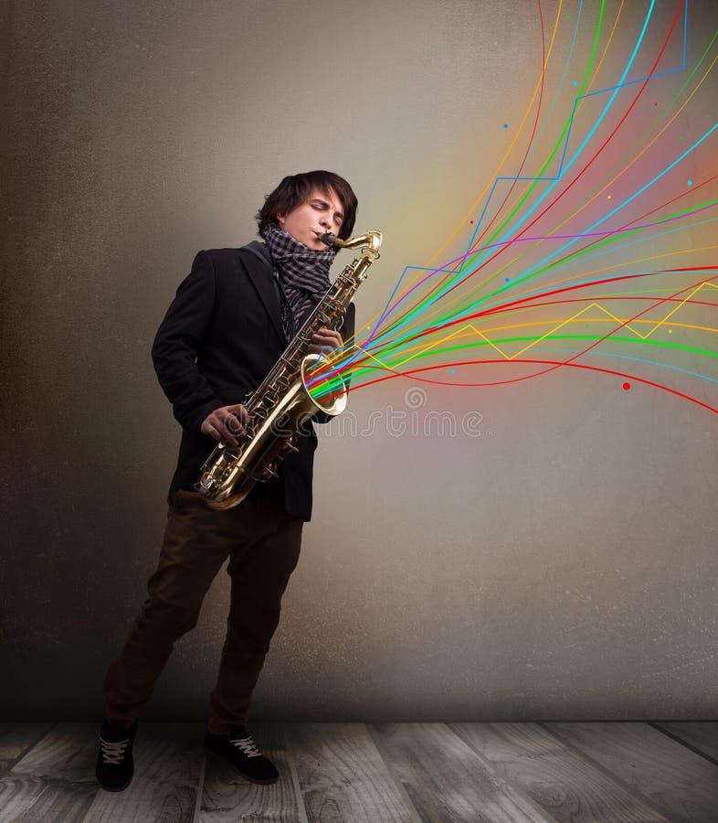 使用在萨克斯管的可爱的音乐家,当五颜六色的摘要时 库存图片