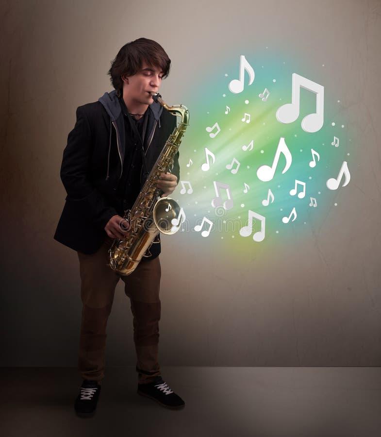 使用在萨克斯管的年轻音乐家,当音符explodin时 免版税库存照片