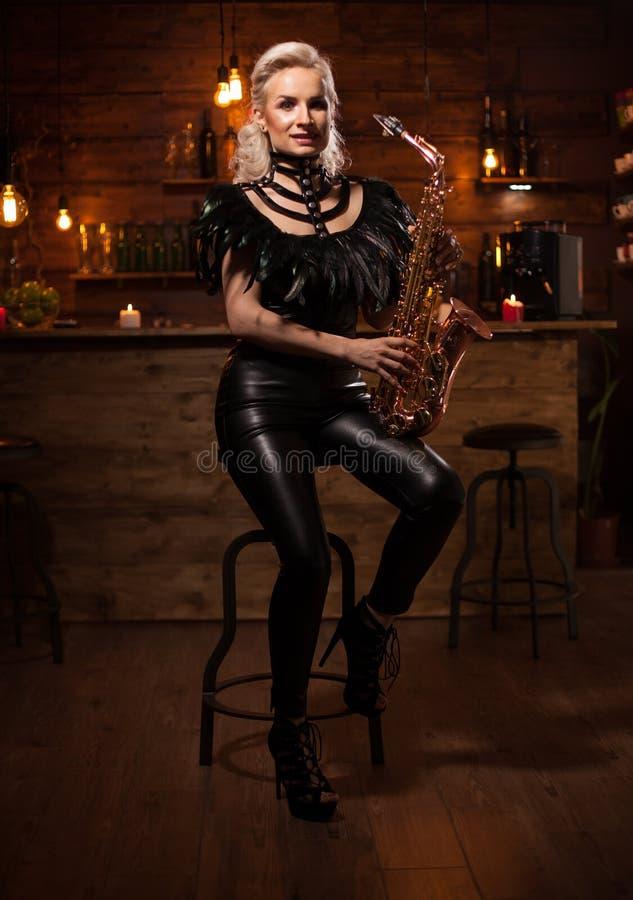 使用在萨克斯管的美丽的年轻女人在葡萄酒客栈 免版税库存照片