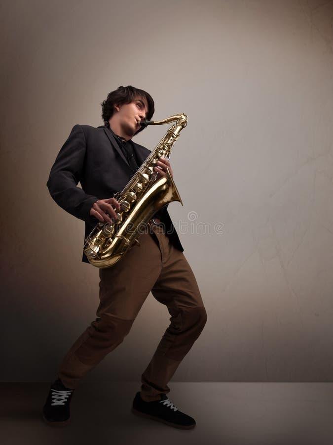 使用在萨克斯管的年轻音乐家 免版税库存照片