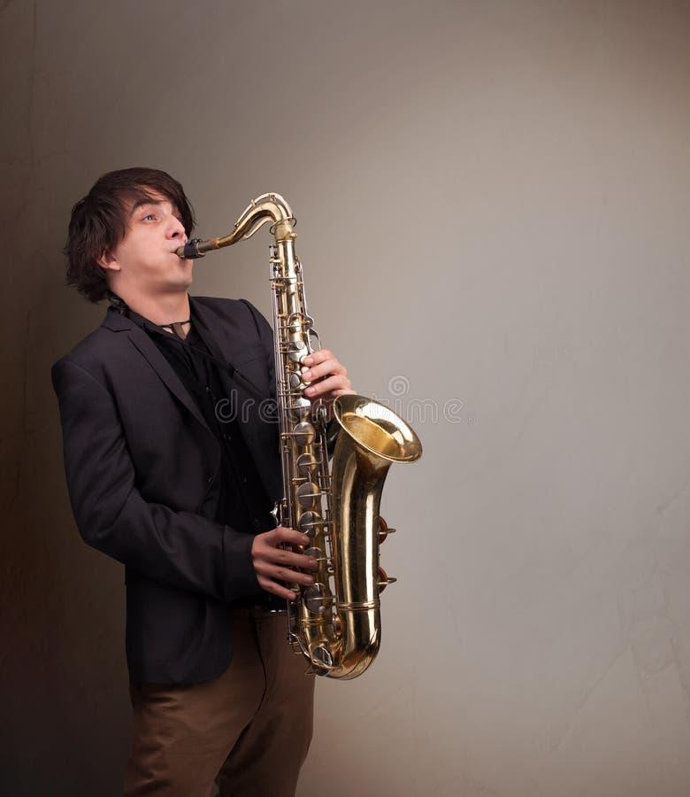 使用在萨克斯管的年轻音乐家 免版税库存图片