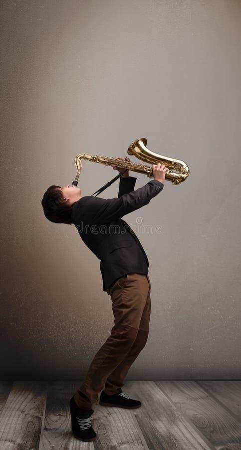 使用在萨克斯管的年轻音乐家 免版税图库摄影