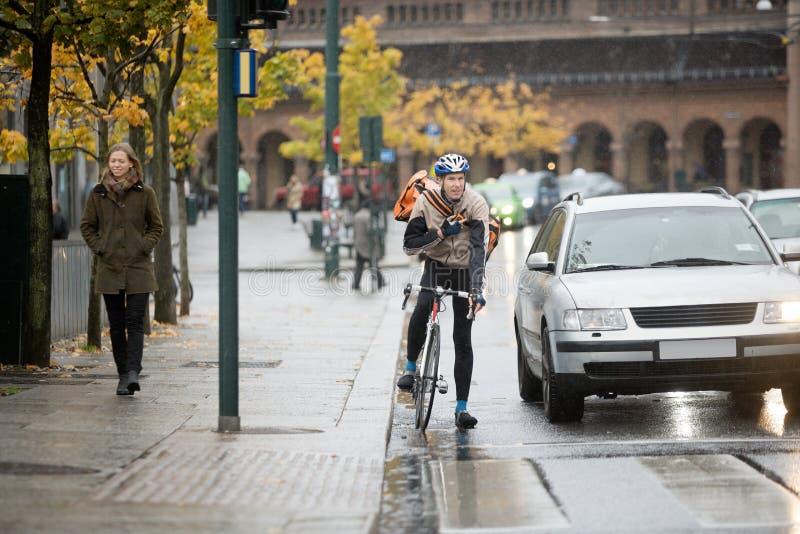使用在街道上的男性骑自行车者携带无线电话 免版税图库摄影