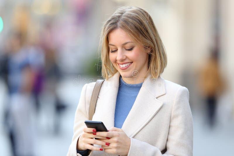 使用在街道上的端庄的妇女一个巧妙的电话 库存照片