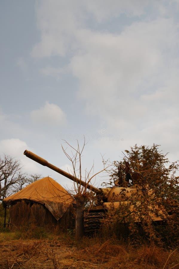 使用在被放弃的俄国军事坦克的安哥拉女孩 免版税库存照片