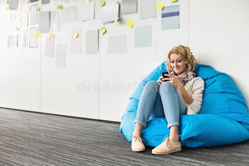 使用在装豆子小布袋椅子的微笑的女实业家手机在创造性的办公室 免版税库存图片