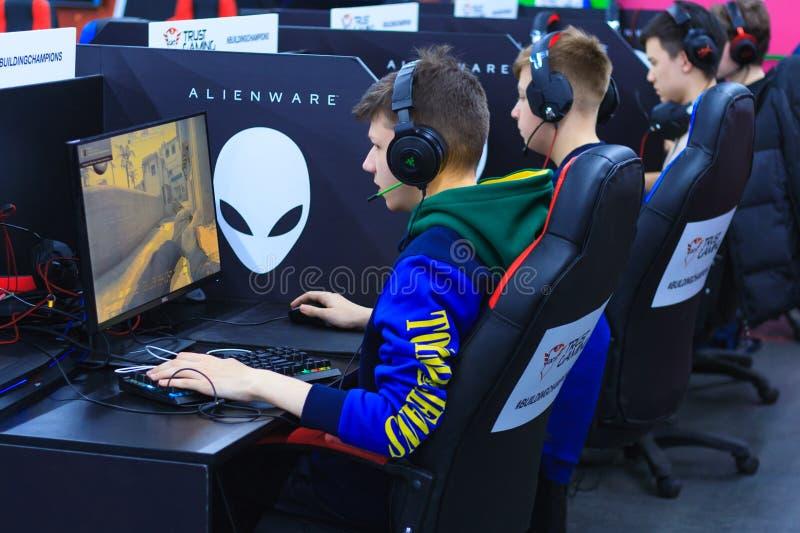 使用在计算机的耳机的年轻游戏玩家 免版税库存图片