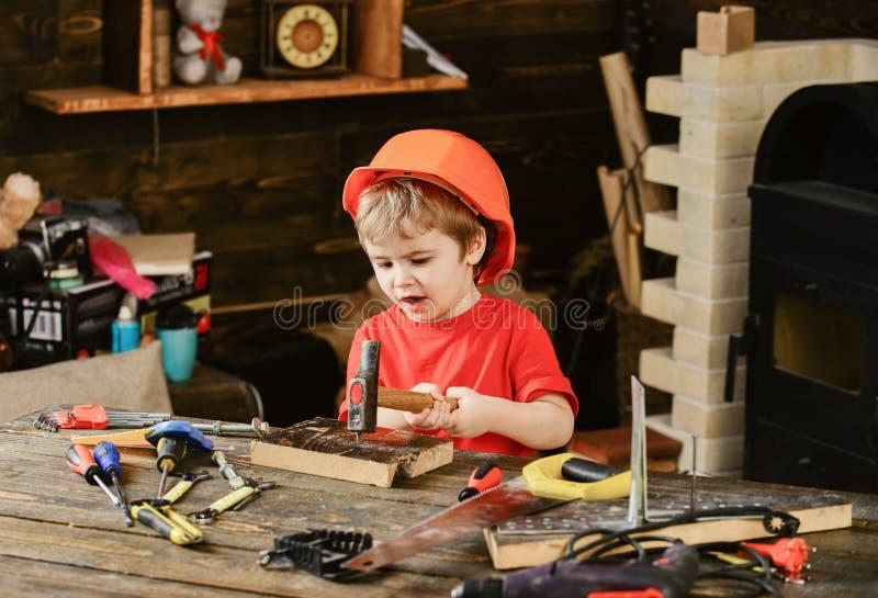 使用在车间的疲乏的孩子 锤击钉子的小男孩 sitiing在运转的书桌的橙色盔甲的小孩 图库摄影