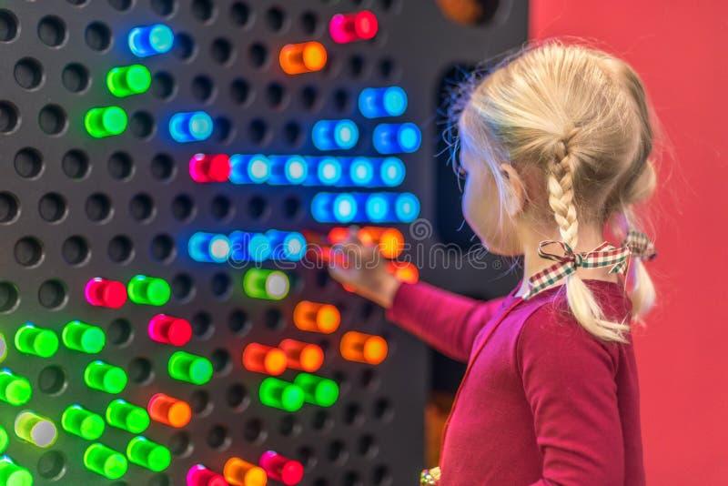 使用在轻的墙壁的小女孩 免版税库存图片