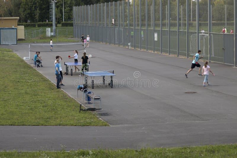 使用在运动场的成人和孩子在公园在夏天晚上 库存图片