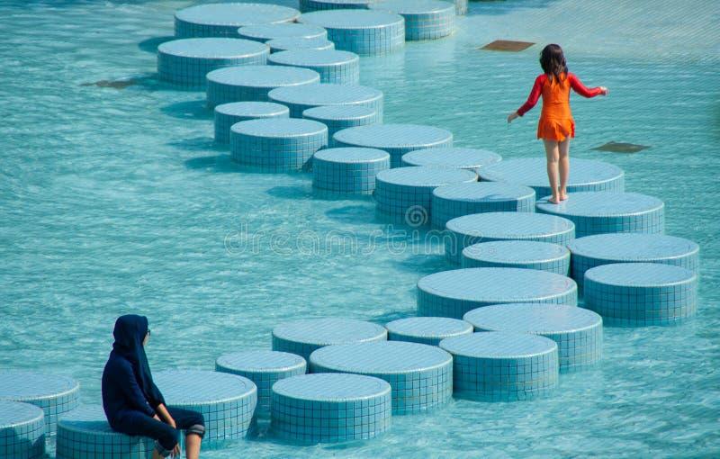 使用在都市水池的两个女孩在吉隆坡 库存照片