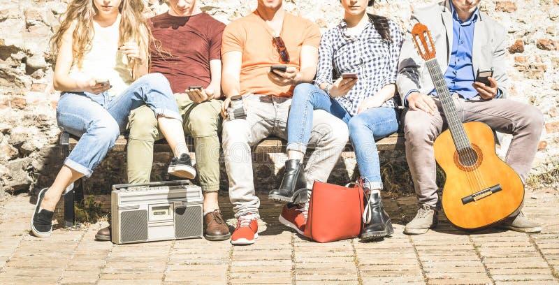 使用在都市背景的小组多文化朋友智能手机 库存照片
