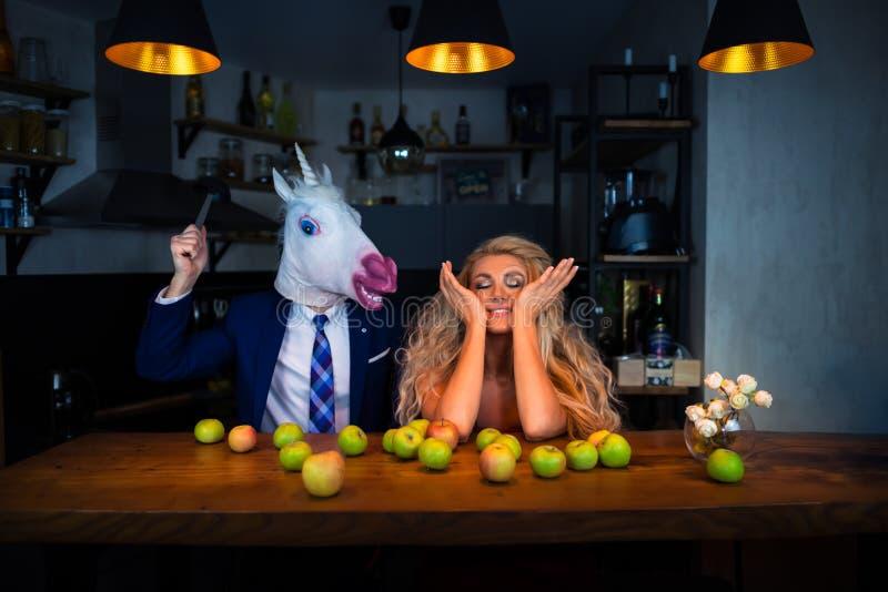 使用在酒吧柜台的滑稽的夫妇在厨房里 图库摄影