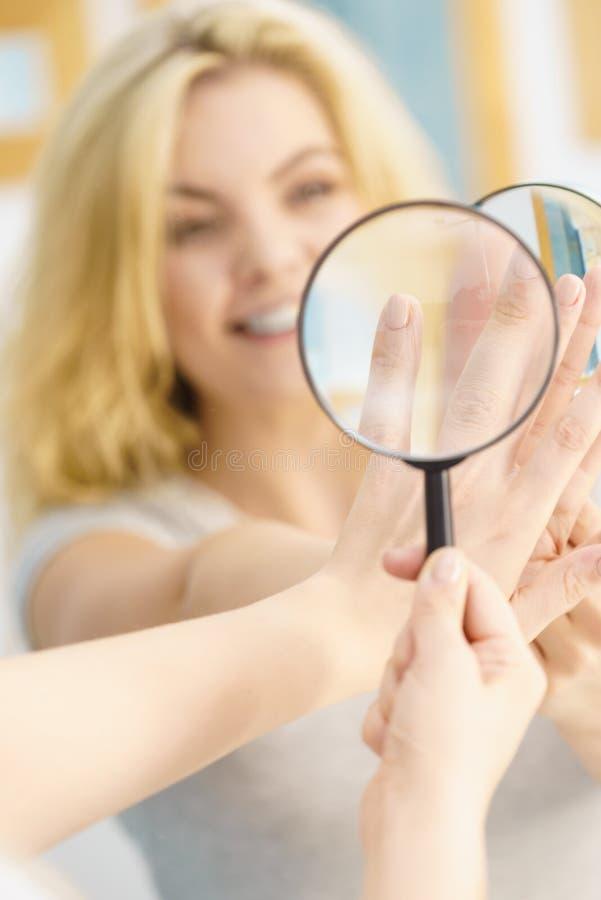 使用在钉子的妇女magnifer 免版税库存图片