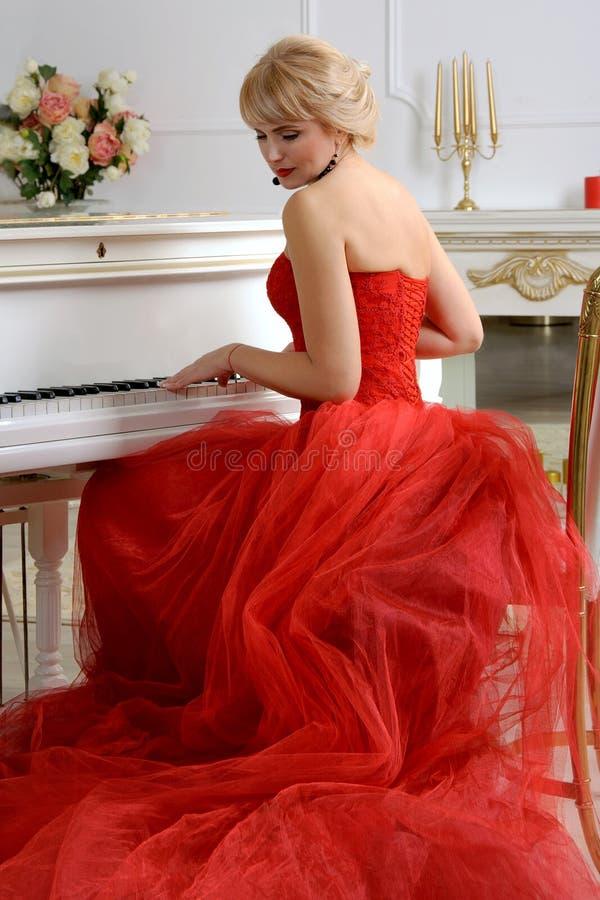 使用在钢琴的一件红色礼服的妇女 免版税库存照片