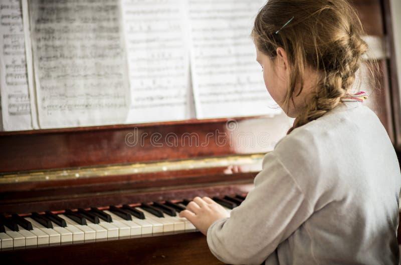 使用在钢琴的孩子女孩 免版税库存照片