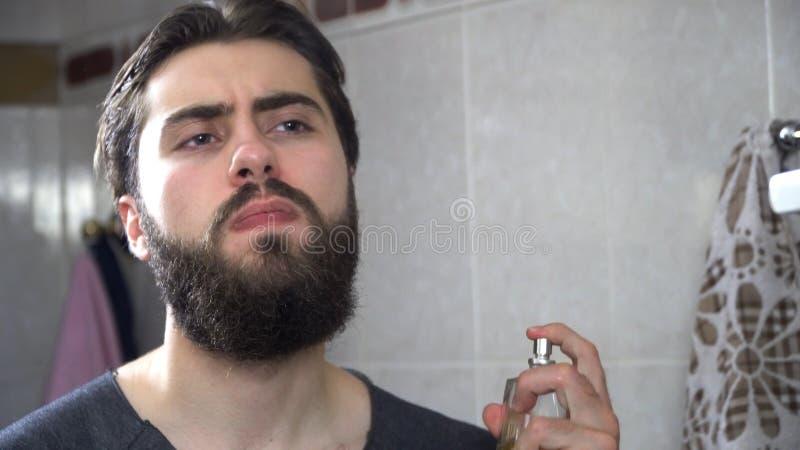 使用在镜子前面的英俊的人香水 应用香水的英俊的人在早晨 免版税图库摄影