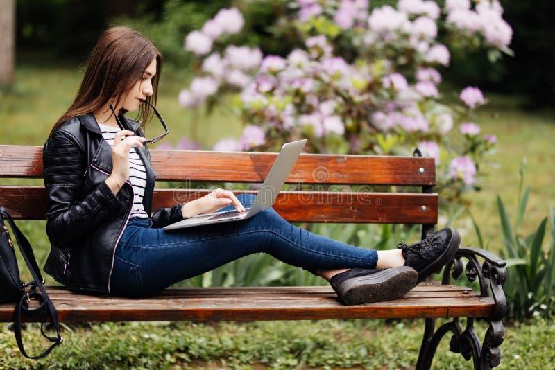 使用在长凳的年轻秀丽学生女孩一台膝上型计算机在公园 免版税库存照片