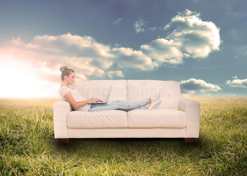使用在长沙发的妇女膝上型计算机在领域 库存照片