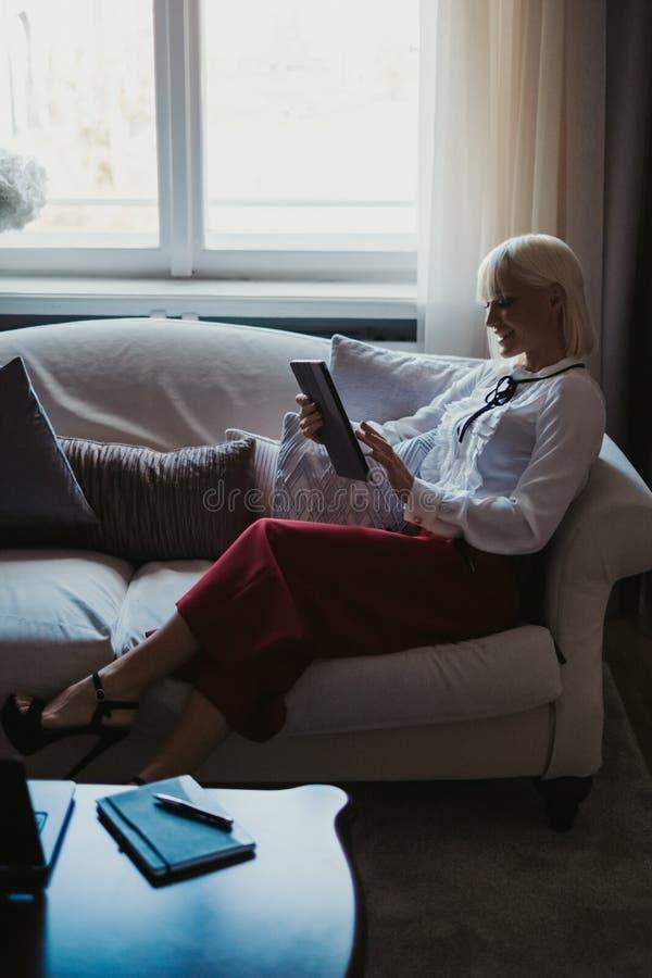 使用在长沙发的微笑的女孩片剂由窗口 免版税图库摄影
