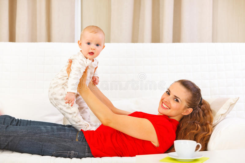 使用在长沙发的微笑的母亲和可爱的婴孩 免版税库存图片