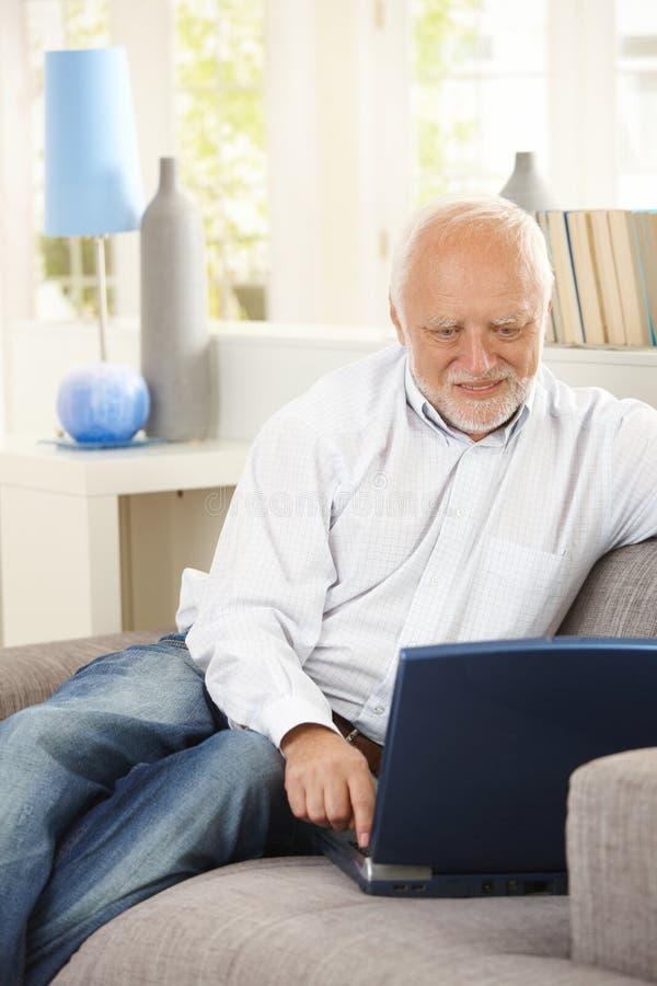 使用在长沙发的快乐的领退休金者膝上型计算机 免版税图库摄影