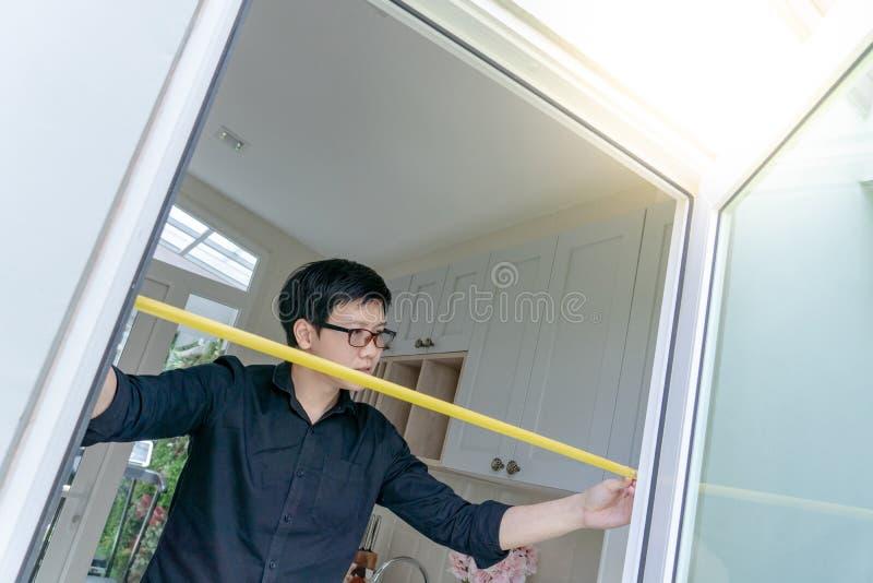 使用在门框的亚裔人卷尺 免版税库存照片