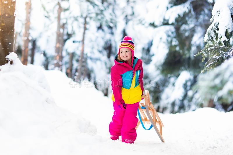 使用在雪橇的雪的孩子在冬天公园 库存照片