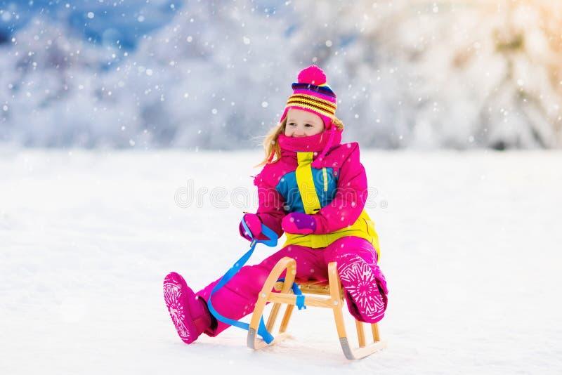 使用在雪橇的雪的孩子在冬天公园 免版税图库摄影
