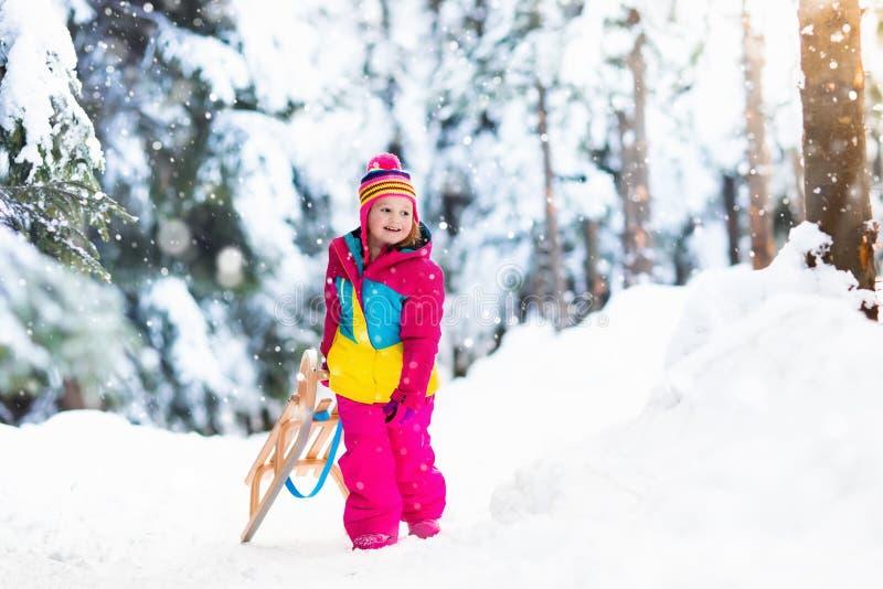 使用在雪橇的雪的孩子在冬天公园 图库摄影