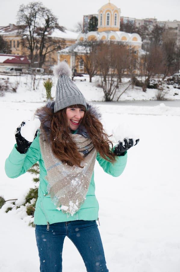 使用在雪球的公园的快乐的女孩 免版税库存图片