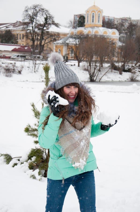 使用在雪球的公园的快乐的女孩 免版税库存照片