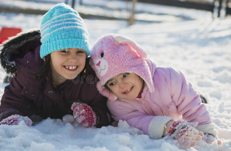 使用在雪的两个滑稽的可爱的妹 库存照片