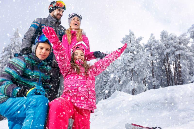 使用在雪的年轻家庭美好的晴朗的冬日胜过 免版税库存照片