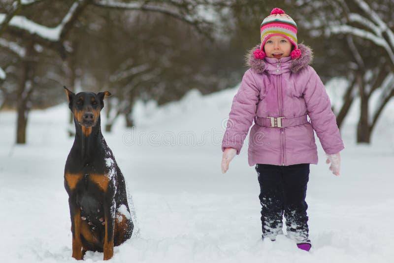 使用在雪的快乐的孩子 获得两个愉快的女孩乐趣在冬日之外 库存照片
