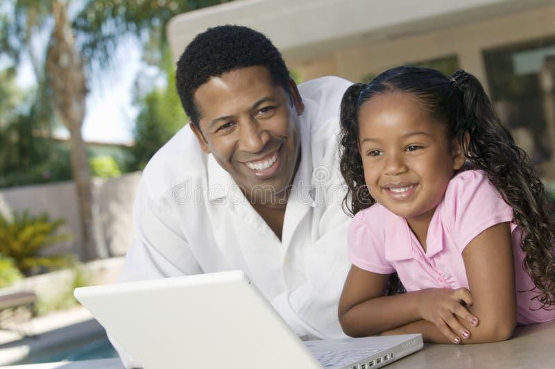 使用在露台画象的父亲和女儿膝上型计算机 库存图片