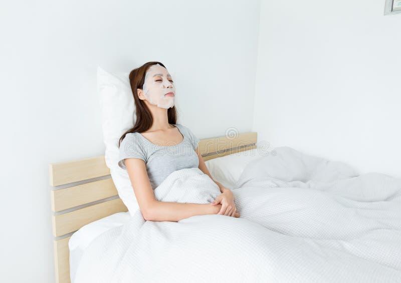 使用在面孔的亚裔妇女纸面具和躺下在床上 免版税库存照片