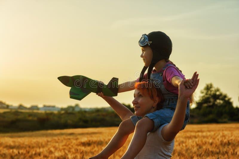 使用在领域的妈妈和女儿在与模型飞机的日落 免版税图库摄影