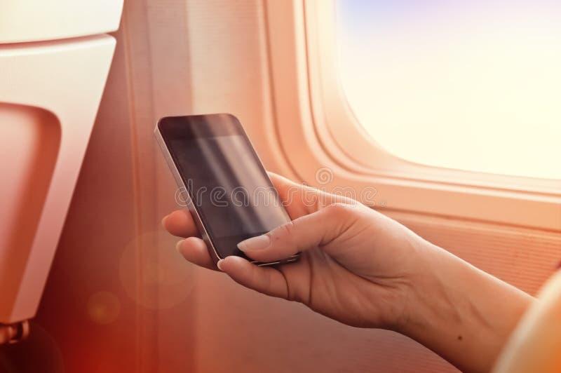 使用在飞机上的机动性 智能手机在妇女手上 库存图片