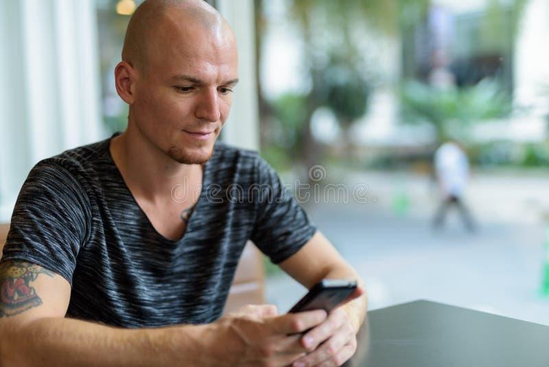 使用在餐馆机智里面的年轻英俊的秃头人手机 免版税库存图片