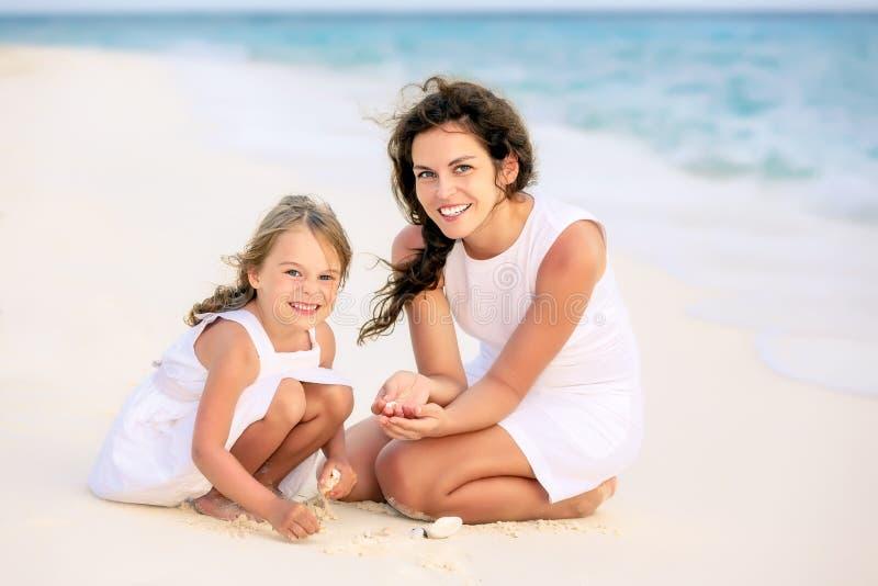 使用在马尔代夫的海滩的母亲和小女儿在暑假 库存图片